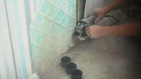 Un uomo taglia un muro di cemento facendo uso di una smerigliatrice di angolo stock footage