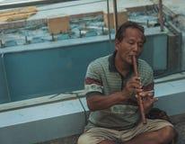 Un uomo tailandese suona per la strada sulle vie di Bangkok immagine stock libera da diritti