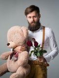 Un uomo tiene con un mazzo delle rose immagine stock libera da diritti