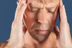 Un uomo tiene le sue mani sulla sua testa su fondo blu Emicrania o emicrania fotografia stock