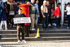 Un uomo tiene un segno che offre comprare i biglietti per il tatuaggio militare a Edimburgo durante il festival 2018 della frangi immagine stock libera da diritti