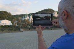 Un uomo tiene una compressa in sue mani Fotografia Stock