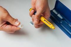 Un uomo tiene una siringa per l'iniezione sottocutanea delle droghe ormonali nella fecondazione in vitro di protocollo di IVF Fotografie Stock