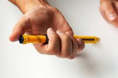 Un uomo tiene una siringa per l'iniezione sottocutanea delle droghe ormonali nella fecondazione in vitro di protocollo di IVF Fotografia Stock