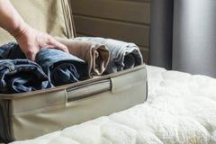 Un uomo tratta le cose Apra la valigia con i vestiti sul letto Vista alla camera da letto Immagini Stock