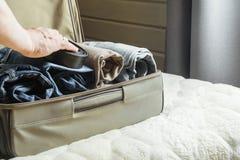 Un uomo tratta le cose Vista alla camera da letto Apra la valigia con i vestiti sul letto Immagini Stock Libere da Diritti