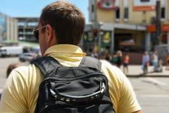 Un uomo turistico con uno zaino nero sta stando vicino ad una strada in un paese caldo immagine stock