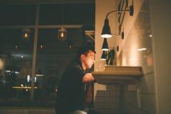 Un uomo in un caffè che si siede ad una tavola di legno con una tazza di cacao Fotografia Stock Libera da Diritti