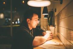 Un uomo in un caffè che si siede ad una tavola di legno con una tazza di cacao Fotografia Stock