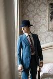 Un uomo in un vestito piacevole sta alla finestra ed allo sguardo al lato Fotografie Stock