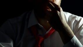 Un uomo in una camicia bianca con una barba segna e tocca la sua barba ed è nervoso fine nera del fondo su, uomo d'affari video d archivio