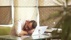 Un uomo in una camicia bianca sta dormendo in un ufficio vicino al suo computer portatile Cattiva condotta, orario di lavoro, int video d archivio