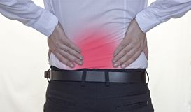 Un uomo in una camicia bianca tiene sopra al dolore alla schiena posteriore e, rosso indietro, uomo d'affari bianco del fondo fotografie stock