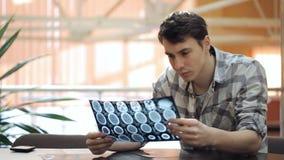 Un uomo in una camicia di plaid esamina in bianco il tomogramma del cervello archivi video