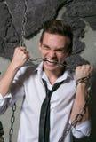 Un uomo in una camicia ed in un legame bianchi rompe i denti a catena Fotografie Stock