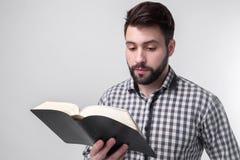 Un uomo in una camicia a quadretti che tiene un libro nero su un fondo leggero Studente barbuto Immagini Stock