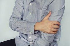 Un uomo in una camicia tiene sopra alla spalla, il braccio, il polso, l'avambraccio, lesione di sport, avvertente il dolore, su u immagini stock libere da diritti