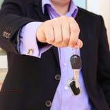 Un uomo in una chiave della tenuta del vestito con telecomando Immagini Stock