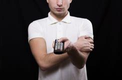 Un uomo in una maglietta bianca con telecomando a disposizione Immagini Stock Libere da Diritti