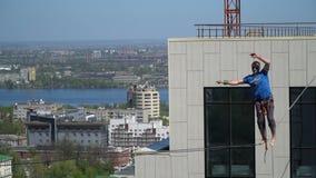 Un uomo in una maglietta blu sta provando a trovare un equilibrio su una corda stretta stock footage