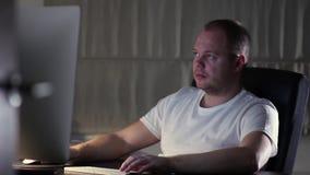 Un uomo in una maglietta lavora a casa al computer stock footage