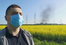 Un uomo in una maschera medica contro lo sfondo della pianta Il concetto di inquinamento ambientale, ecologia immagini stock