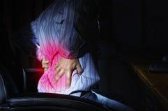 Un uomo in una sedia del computer sul lavoro, soffre da dolore nella parte posteriore immagine stock libera da diritti