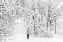 Un uomo in una vista nevosa della foresta da lontano Immagini Stock
