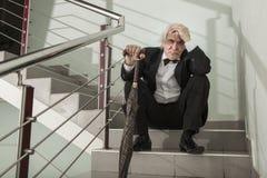 Un uomo in uno smoking su una scala del metallo Fotografie Stock