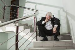 Un uomo in uno smoking su una scala del metallo Fotografia Stock