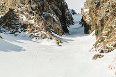 Un uomo uno snowboarder freerider discende un remoto all'alta velocità da un pendio Immagini Stock Libere da Diritti