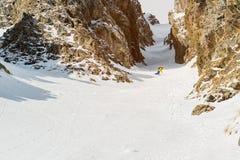 Un uomo uno snowboarder freerider discende un remoto all'alta velocità da un pendio Fotografia Stock