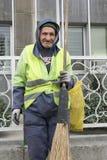 Un uomo urbano anziano dello spazzino che tiene strumento ampio fatto a mano Immagine Stock