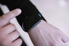 Un uomo utilizza un orologio astuto nella fine nera su immagini stock