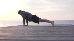 Un uomo va dentro per gli sport al tramonto dal mare video d archivio