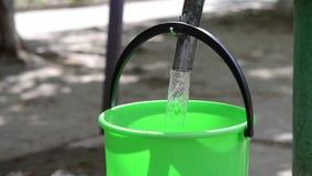 Un uomo versa l'acqua in un secchio di plastica video d archivio