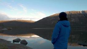 Un uomo in vestiti di sport, esaminanti una bella riflessione dei picchi di montagna nel lago Panorama video d archivio