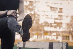 Un uomo in vestiti neri sta esercitandosi all'aperto con una barriera atleta di forma fisica sul campo sportivo addestramento con fotografia stock