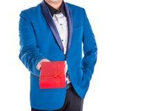 Un uomo in vestito che tiene scatola attuale rossa sopra bianco Fotografia Stock Libera da Diritti