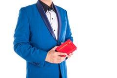 Un uomo in vestito che tiene scatola attuale rossa sopra bianco Fotografie Stock
