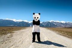 Un uomo in un vestito del panda sta aspettando su una strada vuota contro un fondo delle montagne La Bulgaria, Bansko - 2015 Fotografia Stock Libera da Diritti