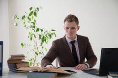Un uomo in un vestito lavora al computer con i libri nell'ufficio fotografie stock libere da diritti
