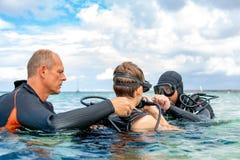 Un uomo in un vestito per l'immersione prepara un ragazzo tuffarsi fotografie stock