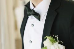 Un uomo in un vestito raddrizza una farfalla sopra immagini stock libere da diritti