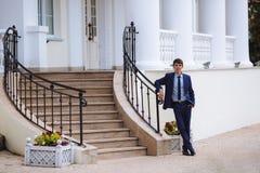 Un uomo in un vestito scuro di affari sta stando alle scale sulla via con le sue gambe attraversate e sta aspettando qualcuno, lu immagini stock libere da diritti