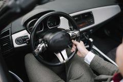 Un uomo in un vestito si siede dietro la ruota di un'automobile immagine stock