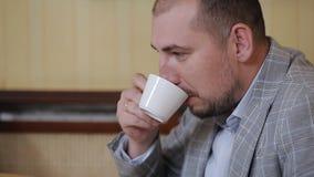 Un uomo in un vestito si siede in un ufficio e beve il caffè mentre esamina un computer portatile stock footage