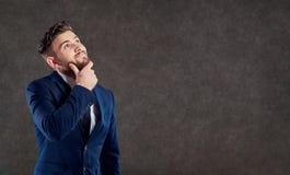 Un uomo in un vestito sta pensando sopra una domanda fotografie stock libere da diritti