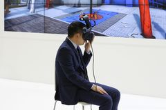 Un uomo in un vestito sta sedendosi su una sedia L'uomo sta indossando i vetri di realtà virtuale fotografia stock libera da diritti