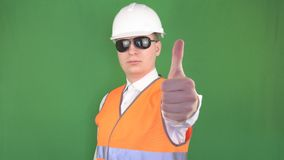 Un uomo in vetri neri ed in un casco protettivo bianco mostra un pollice su alla macchina fotografica, tutto è benissimo, verde archivi video